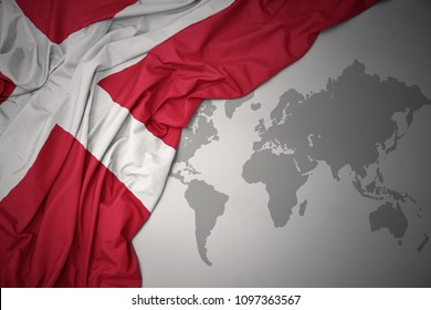 waving colorful national flag of denmark on a gray world map background.