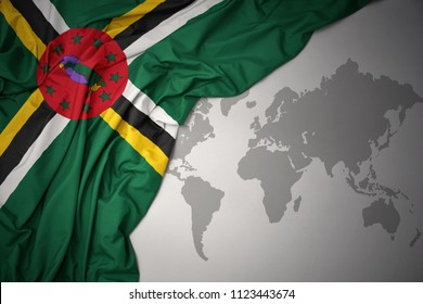 waving colorful national flag of dominica on a gray world map background.