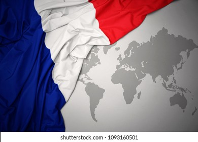 waving colorful national flag of france on a gray world map background.