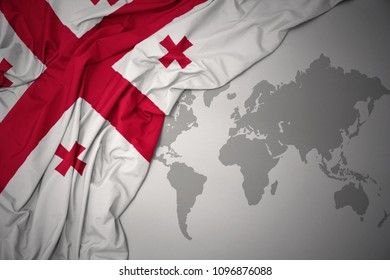 waving colorful national flag of georgia on a gray world map background.