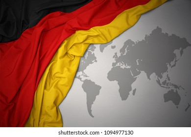 waving colorful national flag of germany on a gray world map background.