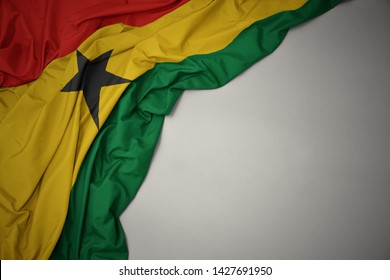 waving colorful national flag of ghana on a gray background.