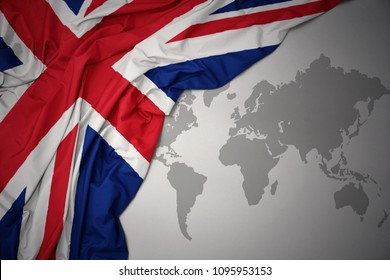 waving colorful national flag of great britain on a gray world map background.