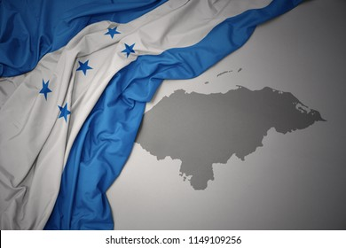 waving colorful national flag of honduras on a gray map background.