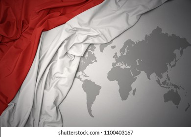 waving colorful national flag of indonesia on a gray world map background.