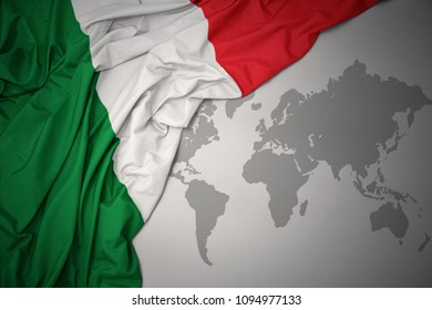 waving colorful national flag of italy on a gray world map background.