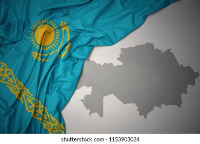 waving colorful national flag of kazakhstan on a gray map background.