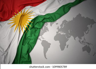 waving colorful national flag of kurdistan on a gray world map background.