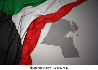 waving colorful national flag of kuwait on a gray map background.