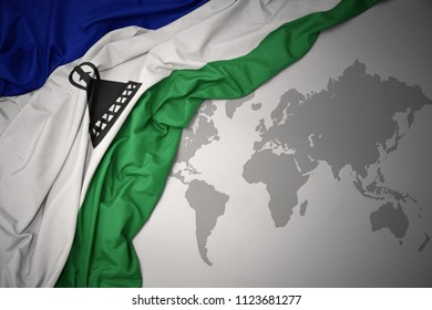 waving colorful national flag of lesotho on a gray world map background.