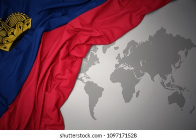 waving colorful national flag of liechtenstein on a gray world map background.