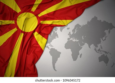 waving colorful national flag of macedonia on a gray world map background.