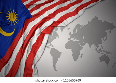 waving colorful national flag of malaysia on a gray world map background.