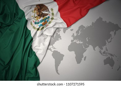 waving colorful national flag of mexico on a gray world map background.