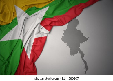 waving colorful national flag of myanmar on a gray map background.