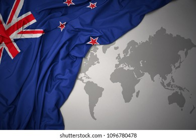 waving colorful national flag of new zealand on a gray world map background.