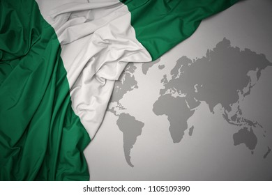 waving colorful national flag of nigeria on a gray world map background.