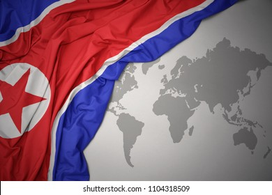 waving colorful national flag of north korea on a gray world map background.