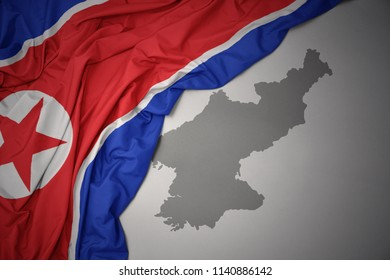 waving colorful national flag of north korea on a gray map background.