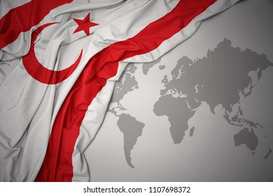 waving colorful national flag of northern cyprus on a gray world map background.