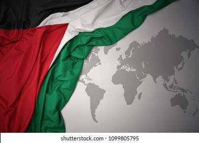 waving colorful national flag of palestine on a gray world map background.