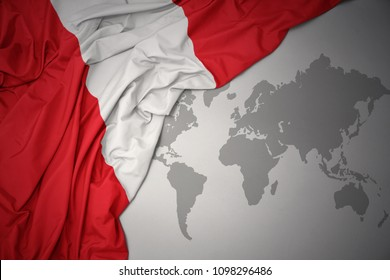 waving colorful national flag of peru on a gray world map background.