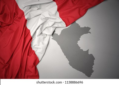waving colorful national flag of peru on a gray map background.