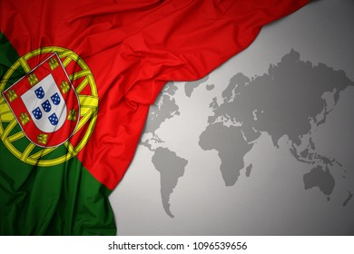 waving colorful national flag of portugal on a gray world map background.
