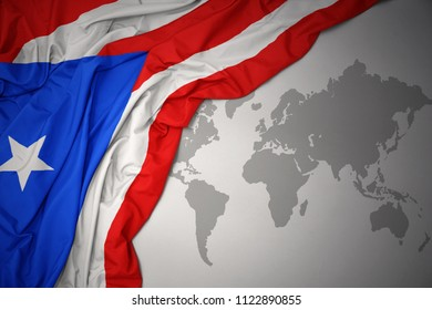 waving colorful national flag of puerto rico on a gray world map background.