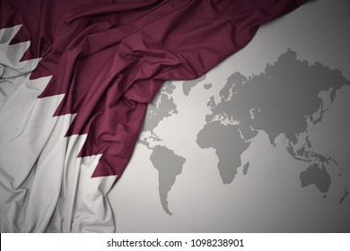 waving colorful national flag of qatar on a gray world map background.