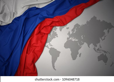 waving colorful national flag of russia on a gray world map background.