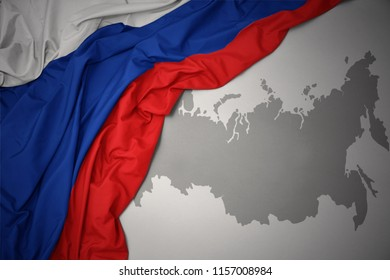 waving colorful national flag of russia on a gray map background.
