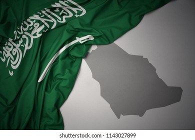 waving colorful national flag of saudi arabia on a gray map background.