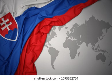 waving colorful national flag of slovakia on a gray world map background.