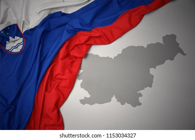 waving colorful national flag of slovenia on a gray map background.