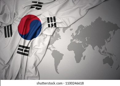 waving colorful national flag of south korea on a gray world map background.