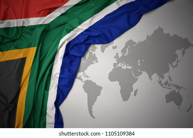 waving colorful national flag of south africa on a gray world map background.