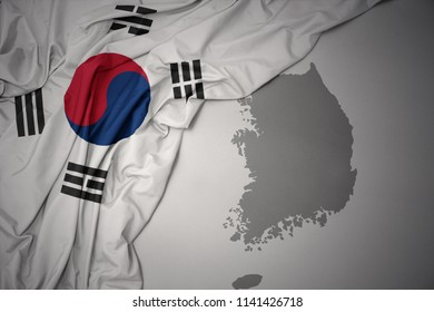 waving colorful national flag of south korea on a gray map background.