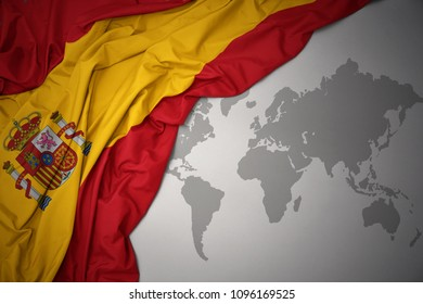 waving colorful national flag of spain on a gray world map background.