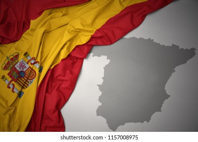 waving colorful national flag of spain on a gray map background.