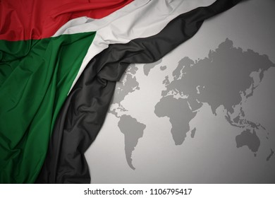 waving colorful national flag of sudan on a gray world map background.