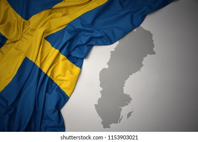 waving colorful national flag of sweden on a gray map background.