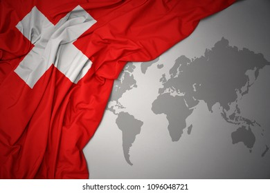 waving colorful national flag of switzerland on a gray world map background.