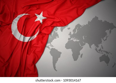 waving colorful national flag of turkey on a gray world map background.