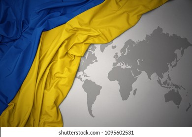 waving colorful national flag of ukraine on a gray world map background.