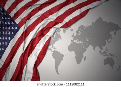 waving colorful national flag of united states of america on a gray world map background.