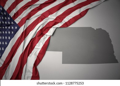 waving colorful national flag of united states of america on a gray nebraska state map background.