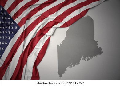 waving colorful national flag of united states of america on a gray maine state map background.