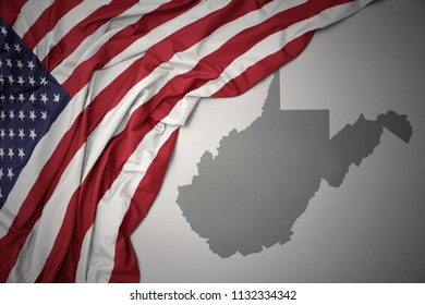 waving colorful national flag of united states of america on a gray west virginia state map background.