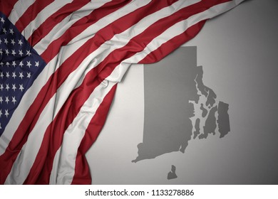 waving colorful national flag of united states of america on a gray rhode island state map background.